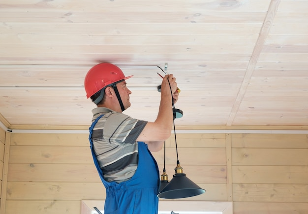 전기 엔지니어가 새 목조 주택에 천장 램프를 설치합니다. 방에 전기 조명 설치