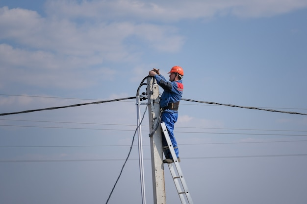 전기 엔지니어는 계단에 서있는 높은 기둥에서 배선을 수행합니다. 고층 전기 작업. 전력선에 podkluchenie 집