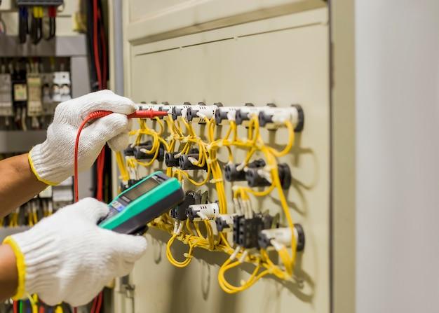 電気技師は、メンテナンスのために定期的に電気制御盤の動作をテストします。