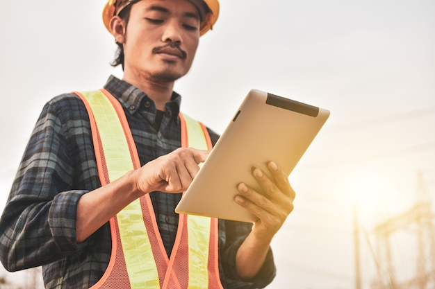 Electrical engineer uses a tablet to inspect power plant network for power generation