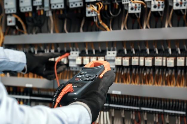 디지털 미터를 사용하여 회로 차단기의 전류 전압을 확인하는 전기 엔지니어.