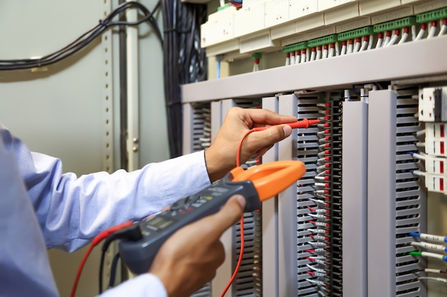 Electrical engineer using digital multi-meter to check current voltage at circuit breaker.