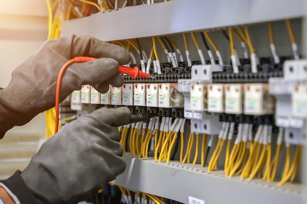 Electrical engineer using digital multimeter to check current voltage at circuit breaker in main distribution board.