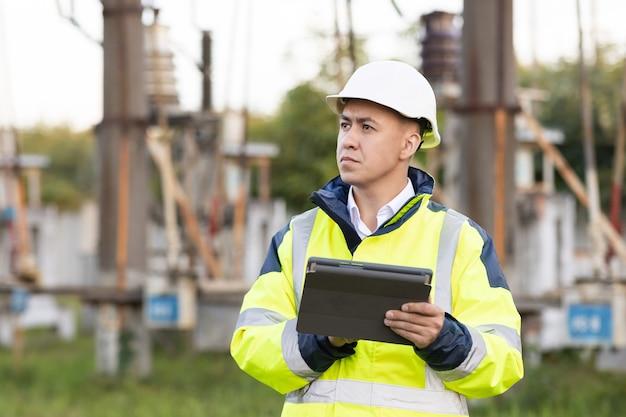 高電圧の電気パイロンを持つ電気技師特別な服を着たエネルギー技師の男