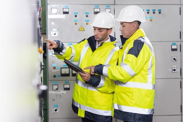 Инженеры-электрики проверяют плату управления с планшетом высоковольтной электростанции
