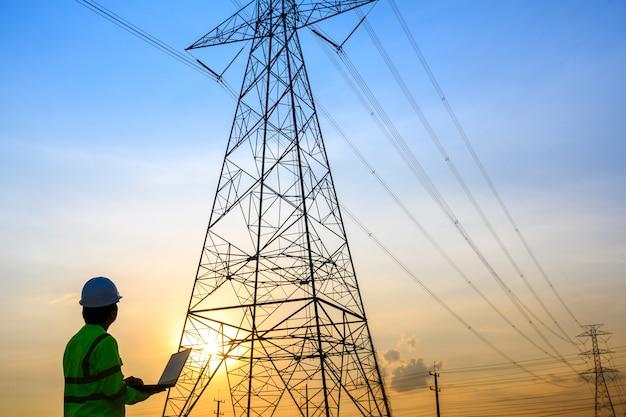 発電所で作業し、話している電気技師は、高圧極での発電計画の運用を確認します。