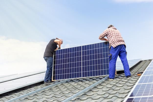 Инженеры-электрики устанавливают солнечные панели на солнечной станции на крыше дома на фоне голубого неба