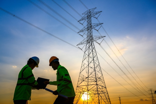 Electrical engineers working and talking power station to see the operation of the power generation planning at the high voltage pole.