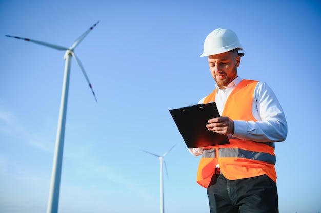 Electrical engineers working at wind turbine power generator station with laptop computer