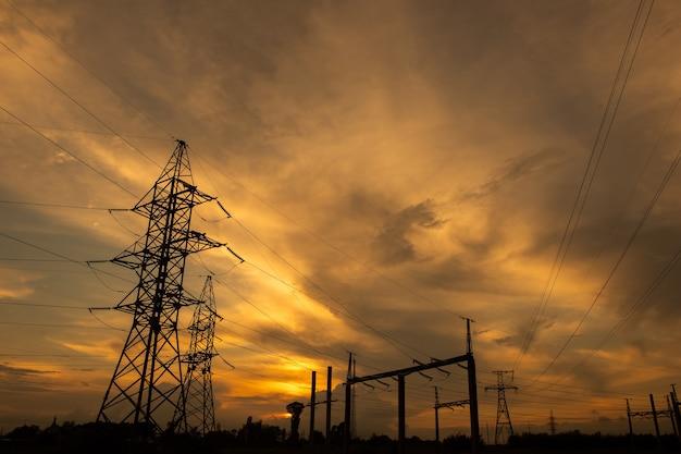 황혼에 전기 그리드 및 전송 라인. 석양 하늘에 대 한 전기 pylons입니다. 하늘을 가로 질러 이동하는 구름. 생태 개념