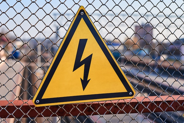 Electrical hazard sign. lightning on yellow background close up.