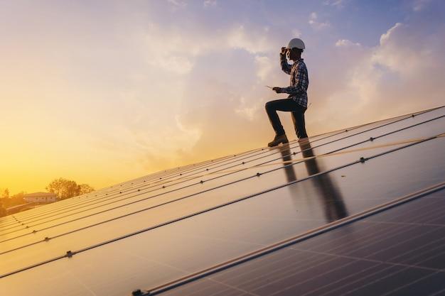 電気機器技術者は、ソーラーパネルフィールドで電気システムのメンテナンスを行った後、リラックスします