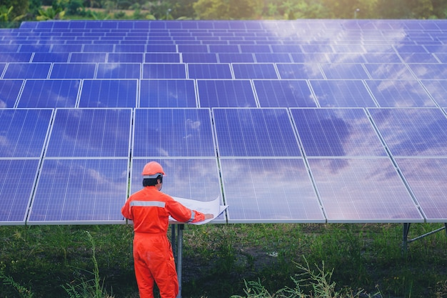 Electrical and instrument technician use blueprint to plan and maintenance electric system at solar panel field