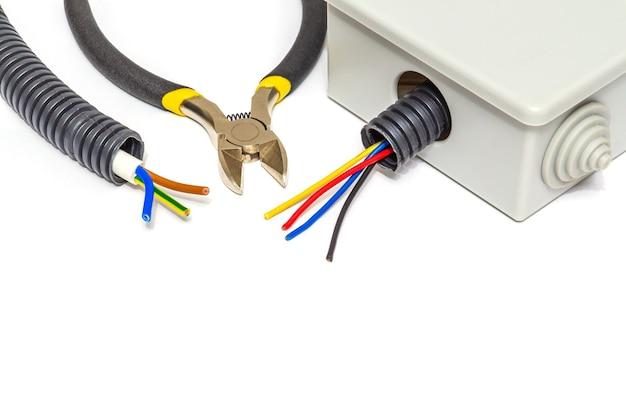 Серая распределительная коробка с проводами, обычно используемыми в процессе электромонтажа на белом изолированном фоне