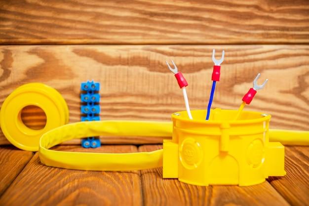 Электрическая распределительная коробка желтого цвета с кабельным проводом, используемым в процессе электромонтажа