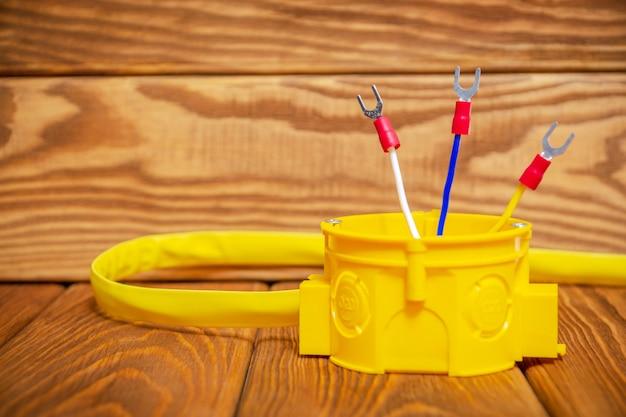 Электрическая распределительная коробка желтого цвета с кабельным проводом, обычно используемая в процессе электромонтажа