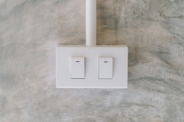 Electrical light switch on cement wall background