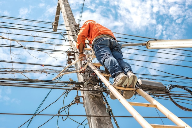 Electrical lineman worker climb a bamboo ladder to repair wire.