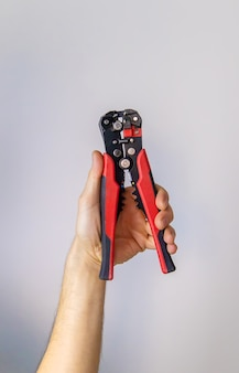 Electrical pliers in the hands of a male isolate. selective focus.