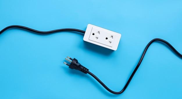 電力ストリップと青色の背景にプラグイン。