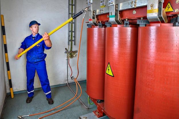 Электробезопасность электрик установит заземление на понижающий силовой трансформатор с помощью hot stick.