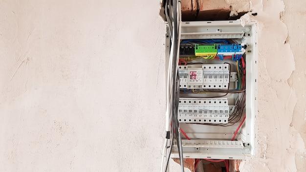 家庭の電気安全、スイッチ付き配電盤パネル。修理中のアパートの家の電気システム。コピースペースのある電気スクリーン内のワイヤー付きサーキットブレーカー。