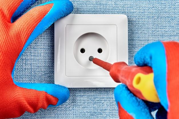 Электрическое обслуживание и ремонт, установка точки питания в домашней электросети, техник закручивает винт на внешней панели розетки.