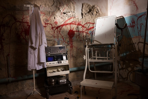 Electrical shocking device near medical gown hanging on the hanger and scary chair with blood stained wall for concept about torture or scary halloween theme