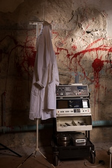 Electrical shocking device near medical gown hanging on the hanger with blood stained wall for concept about torture or scary halloween theme