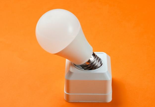 주황색 배경에 전기 소켓 및 led 전구