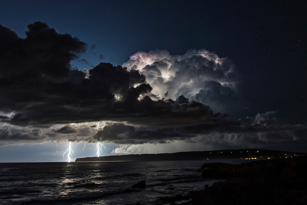 Electrical storm over the mediterranean sea with two lightning strikes falling into the water