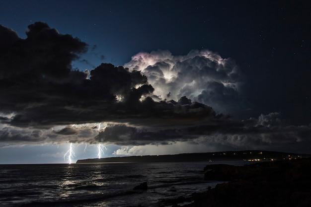 Гроза над средиземным морем с двумя ударами молнии, падающими в воду