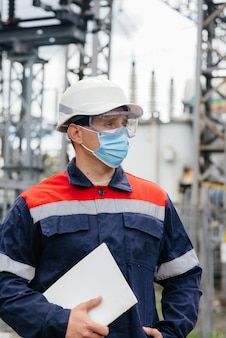 An electrical substation engineer inspects modern high-voltage equipment in a mask at the time of pondemia. energy. industry.