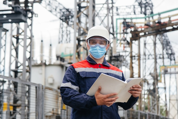 An electrical substation engineer inspects modern high-voltage equipment in a mask