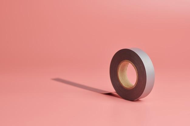 電気テープロール、コピースペース。家のコンセプトのマイナーな修理。最小限のピンクの背景。
