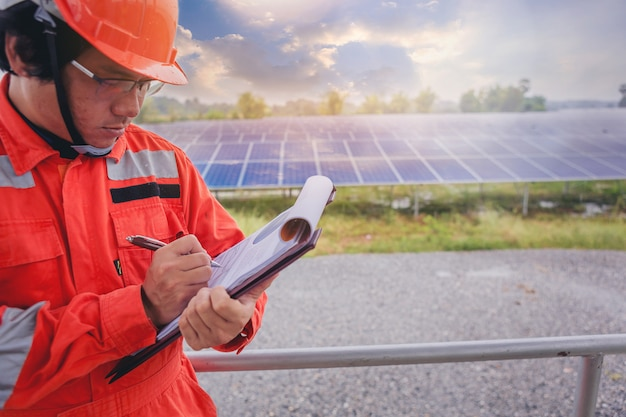 Electrical and technician make a note statistic chart electric system at solar panel field