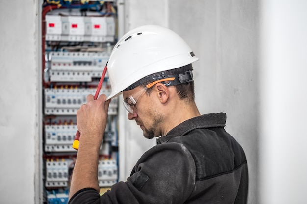 Electrical technician working in a switchboard with fuses