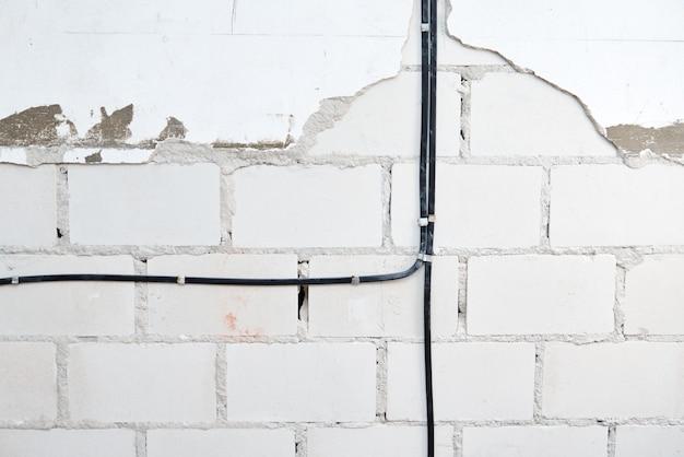 Электрические провода на кирпичной стене. прокладка кабеля