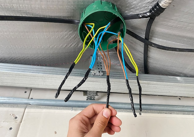 Электропроводка распределительной коробки, установка, закрутка коробки электриком. выборочный фокус.