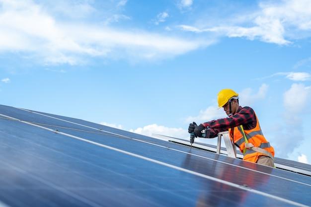 Электрика с техником по приборам, обслуживающим электрическую систему, техник по солнечным батареям со сверлом, устанавливающий солнечные панели на крыше на поле солнечных батарей.