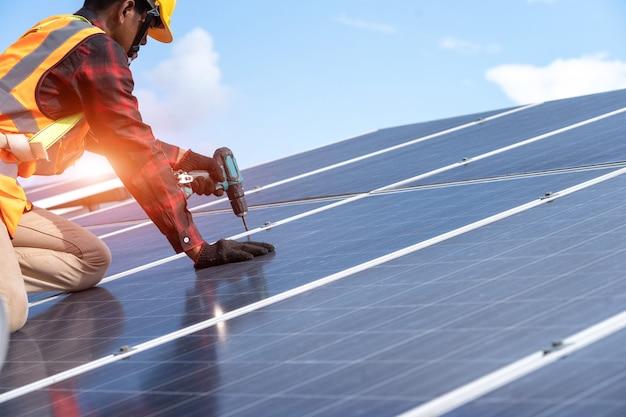 장비 기술자 유지 보수 전기 시스템이 있는 전기, 태양 전지 패널 분야의 지붕에 태양 전지 패널을 설치하는 드릴이 있는 태양 전지 패널 기술자.
