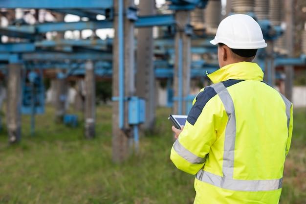 電気労働者エンジニアは、電気エネルギーを使用してタワーの近くでデジタルタブレット電源を使用します