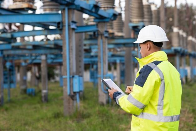 電気エネルギー事業のタワー近くでデジタルタブレットを使用する電気労働者エンジニア