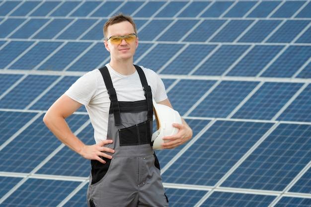 Электромонтажник держит белую защитную шляпу и стоит на электростанции. солнечный инженер в защитных желтых очках и серой спецодежде стоит возле поля солнечных батарей.