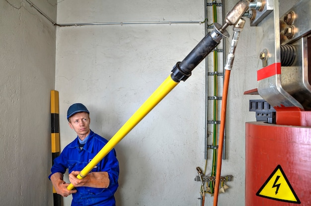 Электротехническая безопасность на рабочем месте инженер-электрик наложил временное заземление на понижающий силовой трансформатор, используя заземляющую разрядную палку.