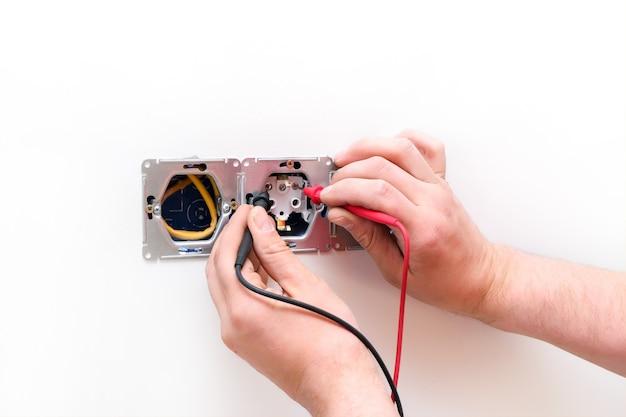 전기 멀티미터가 있는 벽면 소켓입니다. 손에 와이어와 멀티미터를 닫습니다.