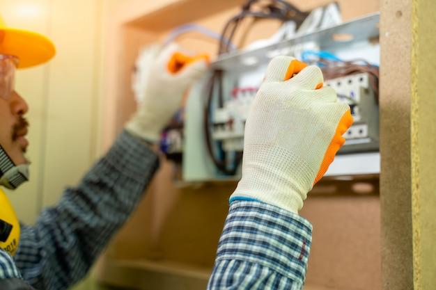 Электрик на работе в доме, электрике ремонтируя электрическую коробку с плоскогубцами в коридоре жилой электрической системы.
