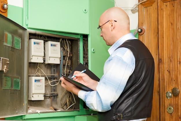 配電用ヒューズボードの高圧送電線のケーブル接続を検査している電気技師