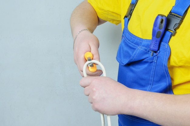 Electrician in a blue jumpsuit and a yellow t-shirt