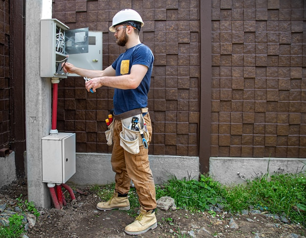 Электрик-строитель за работой, осматривает кабельное соединение в линии электропередачи в фюзеляже промышленного распределительного щита. профессионал в спецодежде с инструментом электрика.